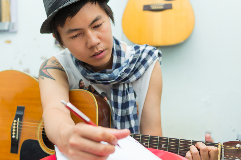 SongwriterLink Shutterstock Man playing guitar with Notebook image 4 Approaches to Writing a Song Songwriting Blog